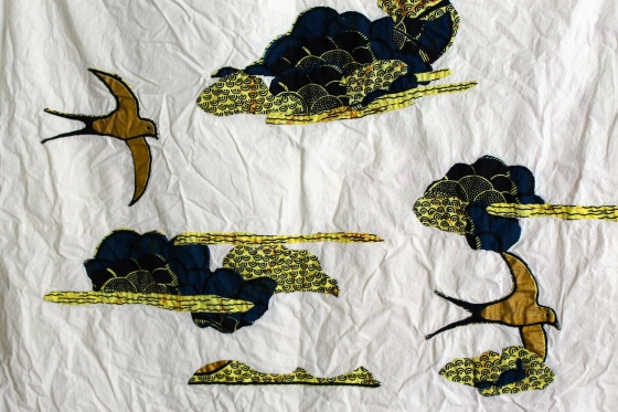 Close up of quilt top with gold birds and indigo clouds appliquéd on it