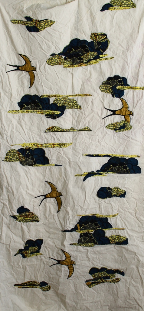 Quilt top with gold birds and indigo clouds appliquéd on it