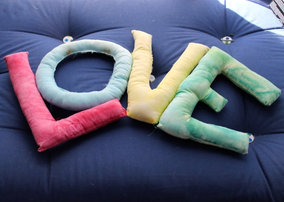 """Stuffed sewn letters spelling out """"love"""""""