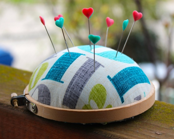 Pincushion made from yellow and green text fabric, with embroidery hoop base and heart pins stuck in it
