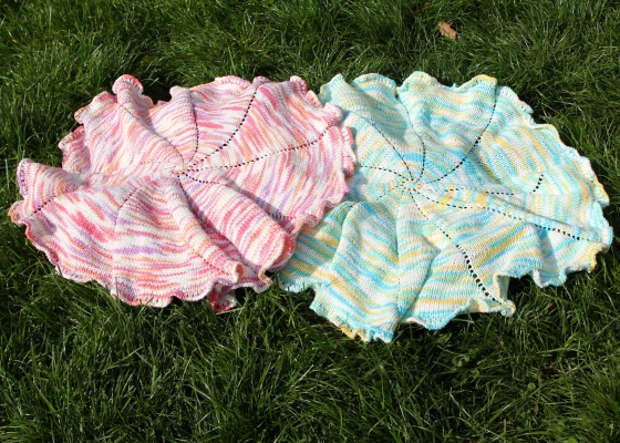 Two spiral knit baby blankets, one in pink cotton yarn and one in blue cotton yarn