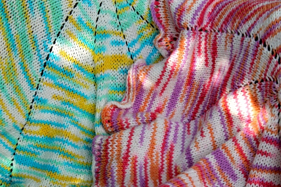 Close up of two spiral knit baby blankets, one in pink cotton yarn and one in blue cotton yarn