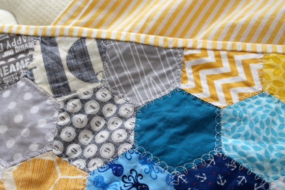 close up of yellow striped binding on queen sized hand pieced quilt made with blue, gray, and yellow hexagons