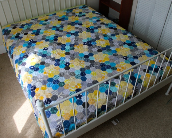 Queen sized hand pieced quilt made with blue, gray, and yellow hexagons, spread over a white bed frame