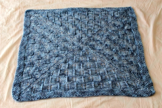 Blue hand knit lacy baby blanket, made with Cascade Yarns