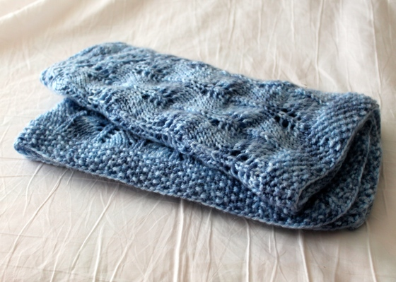 Folded blue hand knit lacy baby blanket, made with Cascade Yarns