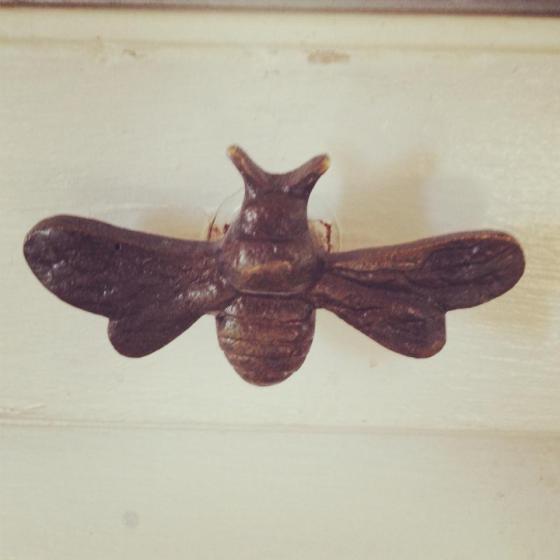 Brass door pull shaped like a bee