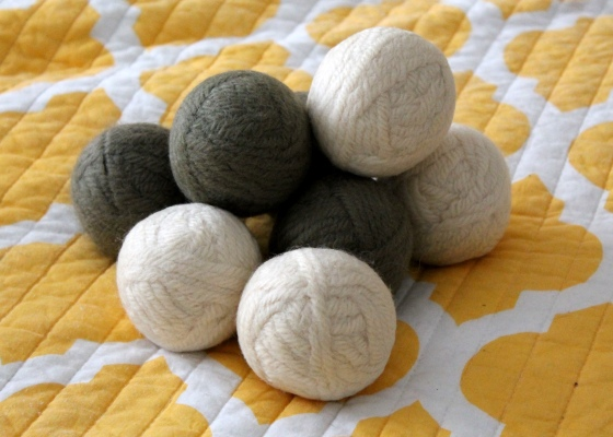 Homemade dryer balls from wool yarn on yellow and white background