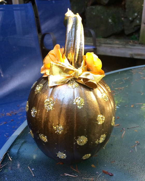 Pumpkin painted bronze with glitter polka dots and a bow