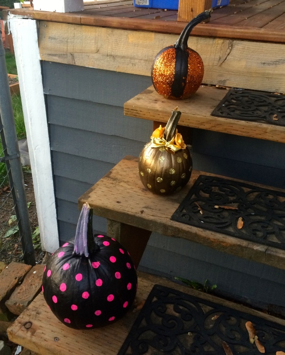 Painted and glittered pumpkins sitting on front steps