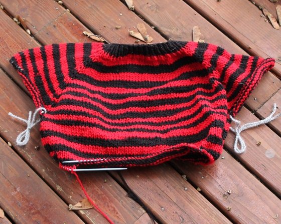 Halfway done knit red and black striped sweater