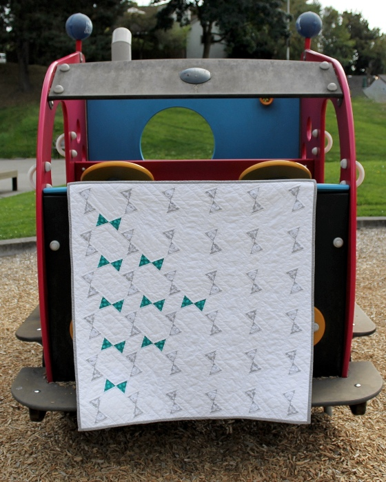Gray and teal modern baby quilt hanging in a playground