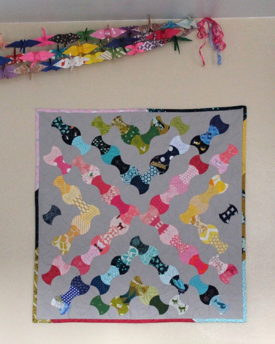 Kaleidoscope wall hanging using paper pieced apple cores, hanging with colorful paper cranes
