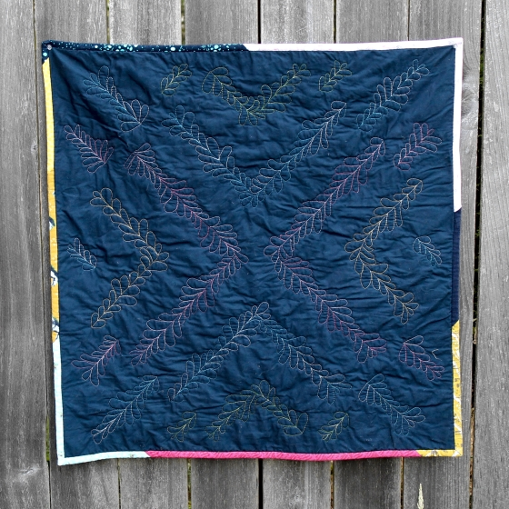 Free motion feather quilting in variegated thread on navy fabric