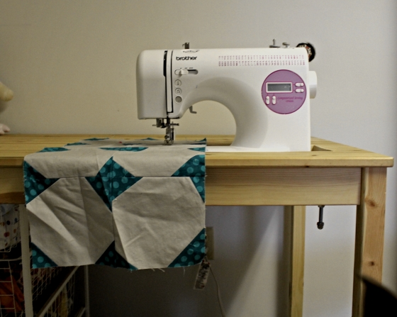 Sunken sewing table with gray and teal project on it