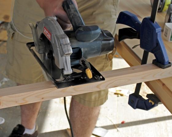 Man cutting furring strips with electric saw